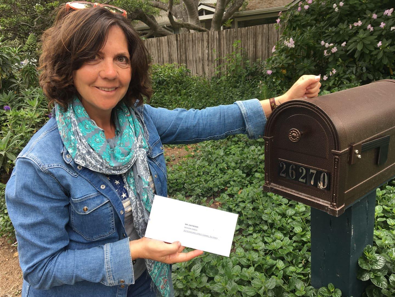 Marta Arroyo, ex alcaldesa de Salas dejando la carta en el Buzón de la casa de Clint Eastwood.